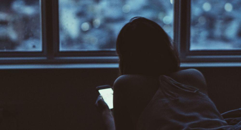 Девушка за смартфоном лежит в кровати. Архивное фото