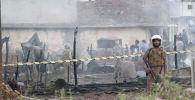 Пакистанские солдаты стоят на страже у поврежденной крыши после того, как военный самолет во время учебного полета разбился в районе застройки в гарнизонном городе Равалпинди. Пакистан, 30 июля 2019 года