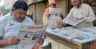 Индийские мужчины читают газеты, в которых публикуются первые новости о взрывах в Пасхальное воскресенье в Шри-Ланке, в придорожном киоске в Амритсаре 22 апреля 2019 года.