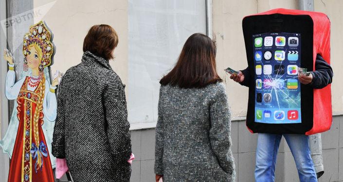 Промоутер в костюме смартфона с треснувшим экраном раздает рекламные листовки на улице Москвы.