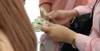 Женщина считает доллары. Архивное фото