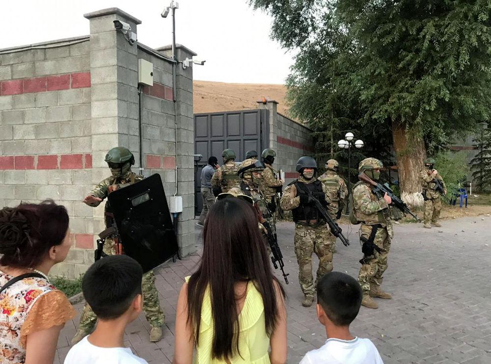 На фотографии спецназ не подпускает мирных жителей, среди которых дети, к территории резиденции экс-президента Кыргызстана Алмазбека Атамбаева во время штурма в селе Кой-Таш 7 августа 2019. Позже туда пришли женщины, чтобы найти своих детей и родственников.