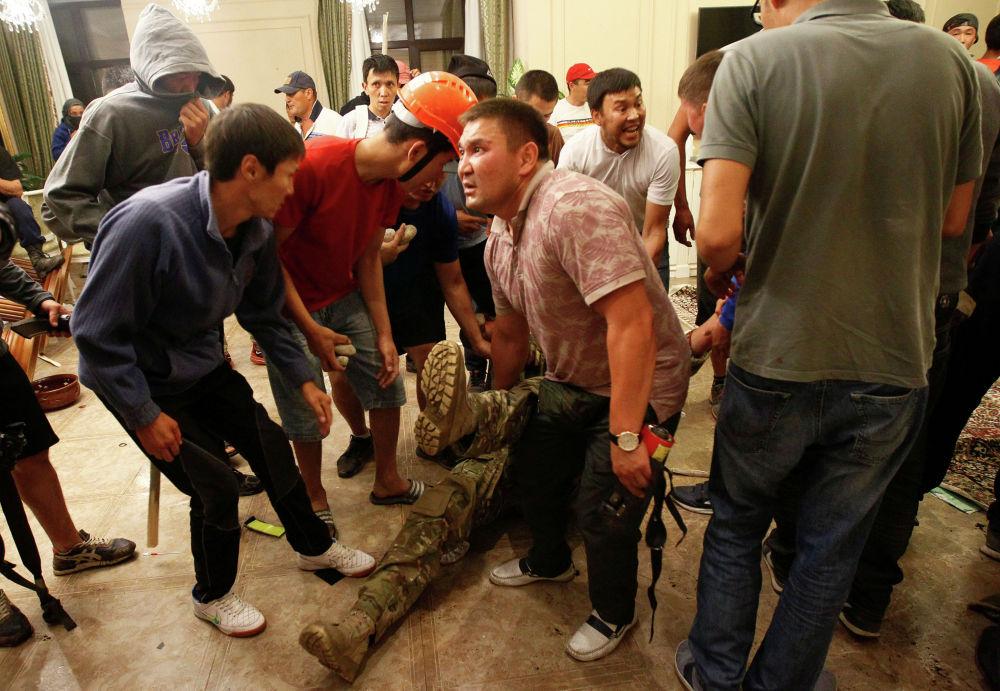 Люди за ногу тащат раненого сотрудника сил национальной безопасности