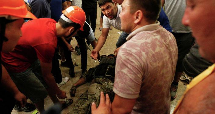 Сторонники бывшего президента Кыргызстана Алмазбека Атамбаева окружают сотрудника сил государственной безопасности, который был ранен во время операции по задержанию Атамбаева