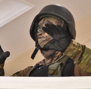 Член кыргызского спецназа сдается сторонникам бывшего президента Алмазбека Атамбаева в его резиденции в селе Кой-Таш под столицей Бишкек 7 августа 2019 года.