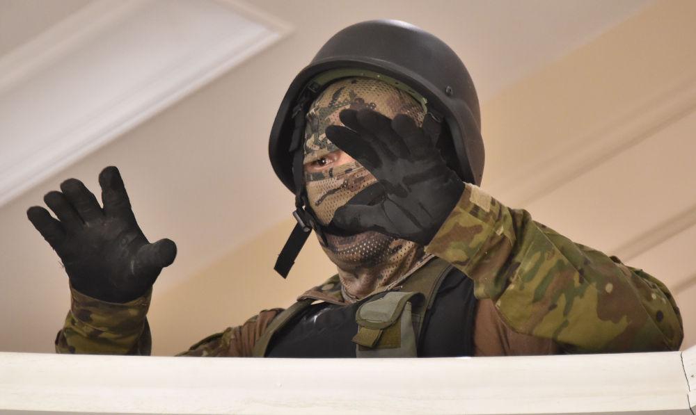 Спецназовец сдается сторонникам бывшего президента в его доме. Позже раненых спецназовцев выводили из дома и сажали в карету скорой медицинской помощи, других взяли в плен.