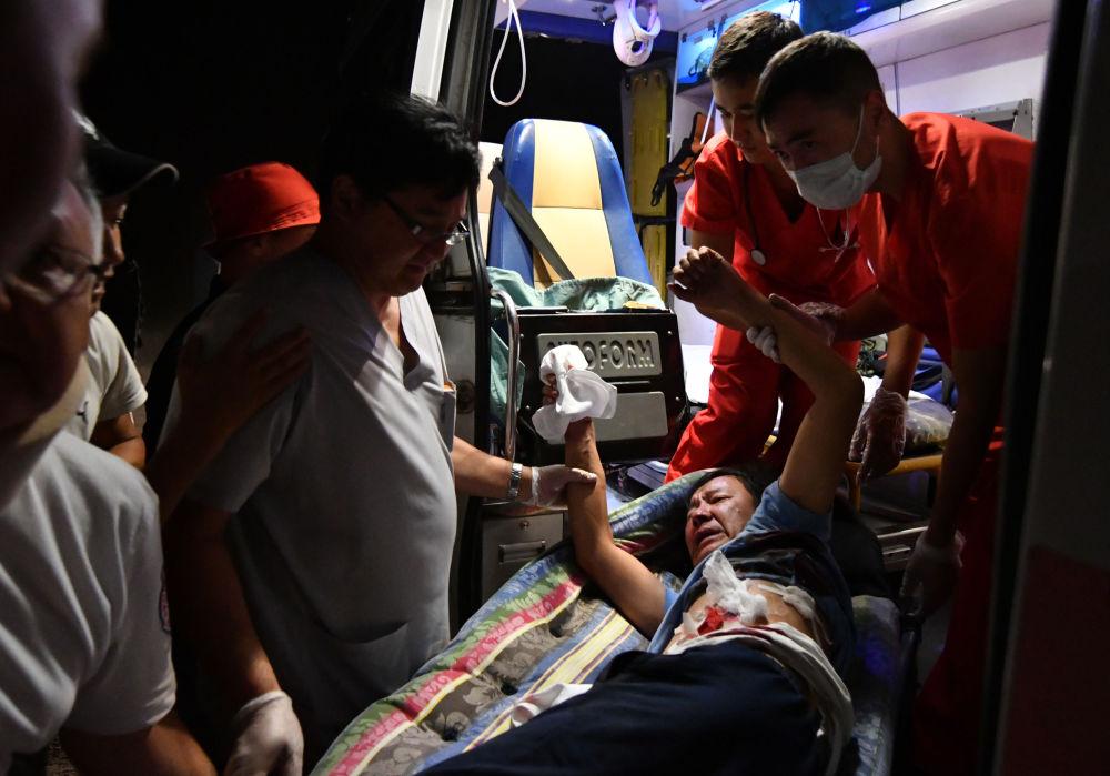 В карете скорой медики оказывают помощь пострадавшему во время операции спецслужб по задержанию экс-лидера Алмазбека Атамбаева