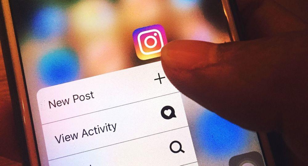Человек нажимает на значок Instagram на мобильном телефоне. Архивное фото