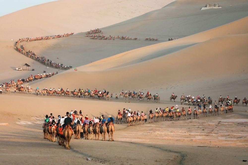 Туристы на верблюдах в пустыне китайского уезда Дуньхуан.