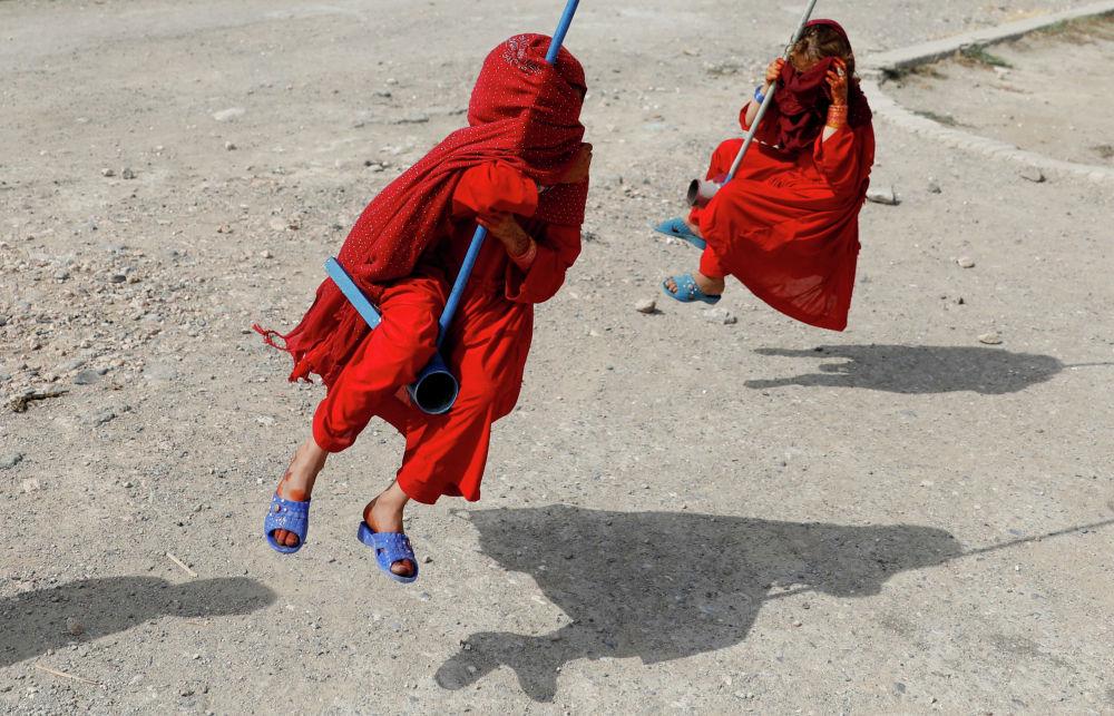 Дети катаются на качелях в первый день мусульманского праздника Курбан-байрам в Кабуле, Афганистан