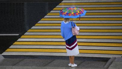 Женщина у пешеходного перехода во время дождя. Архивное фото