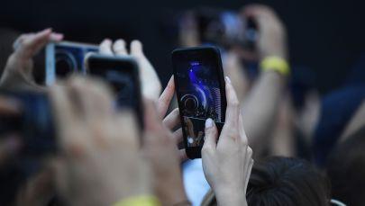 Телефондун камерасына тартып жаткан адамдар. Архив