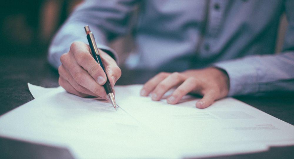 Офисный служащий подписывает документ. Архивное фото