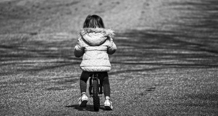 Девочка на детском велосипеде катается по дороге. Архивное фото