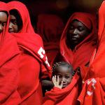 Мигранты ожидают высадки из спасательного катера в порту испанской Малаги