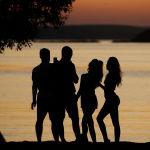 Молодые люди смотрят закат на озере под Минском