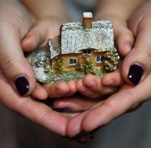 Женщина с ребенком держат макет дома. Архивное фото