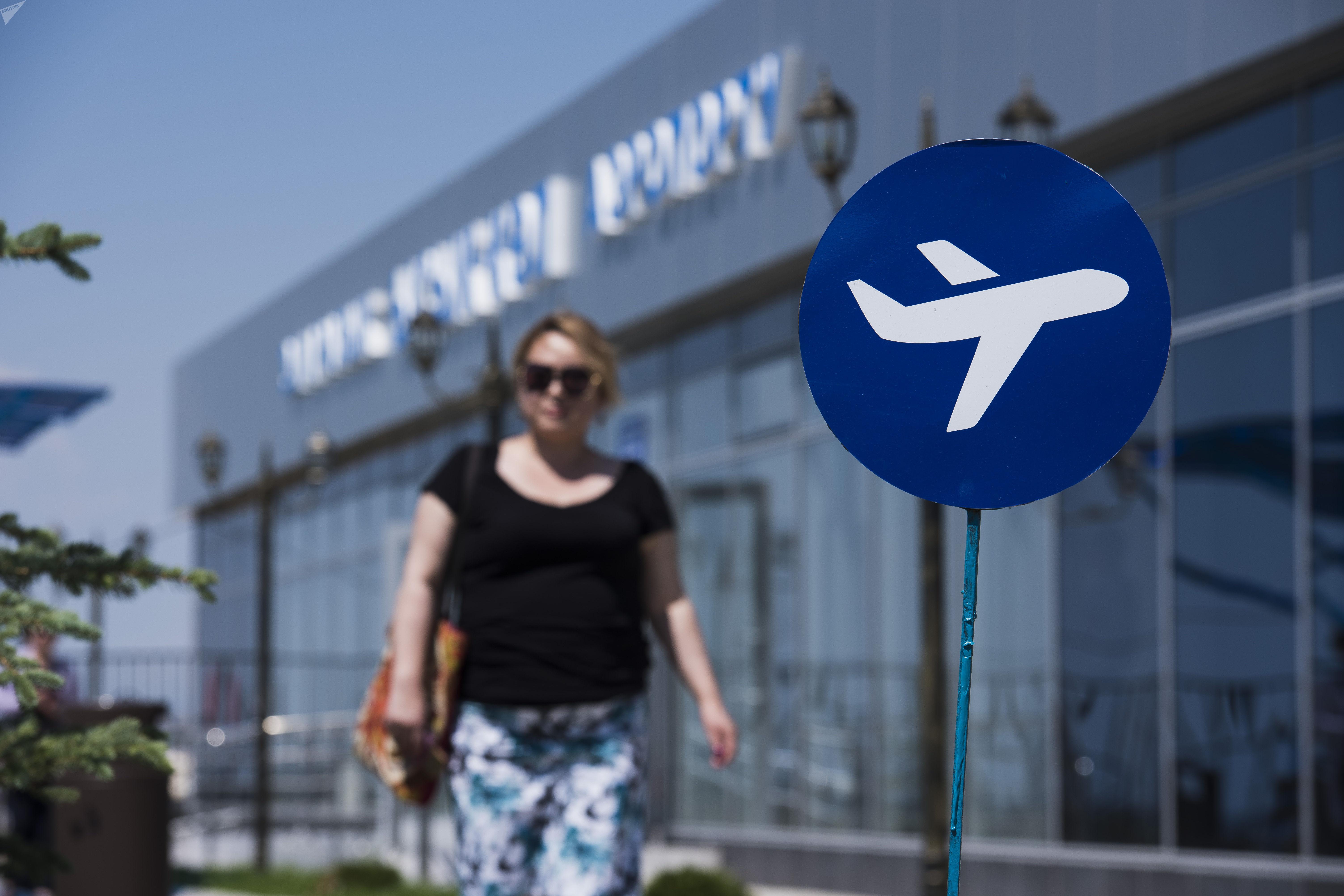 Женщина около дорожного знака на международном аэропорту в селе Тамчи, Иссык-Кульской области