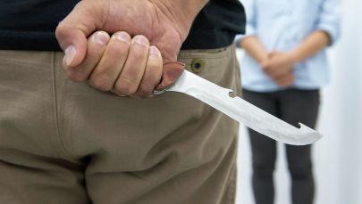 Мужчина показывает нож . Иллюстративное фото