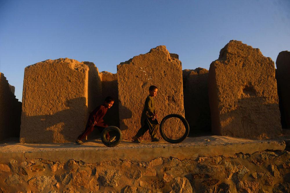 Афганские мальчики играют с шинами на окраине города Герат