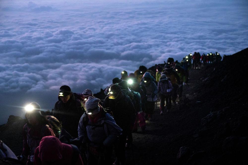 Группа туристов поднимается на вершину вулкана Фудзияма в Японии