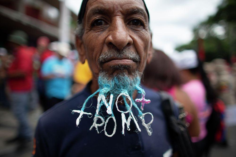 Сторонник президента Венесуэлы Николаса Мадуро на антиамериканском митинге в Каракасе