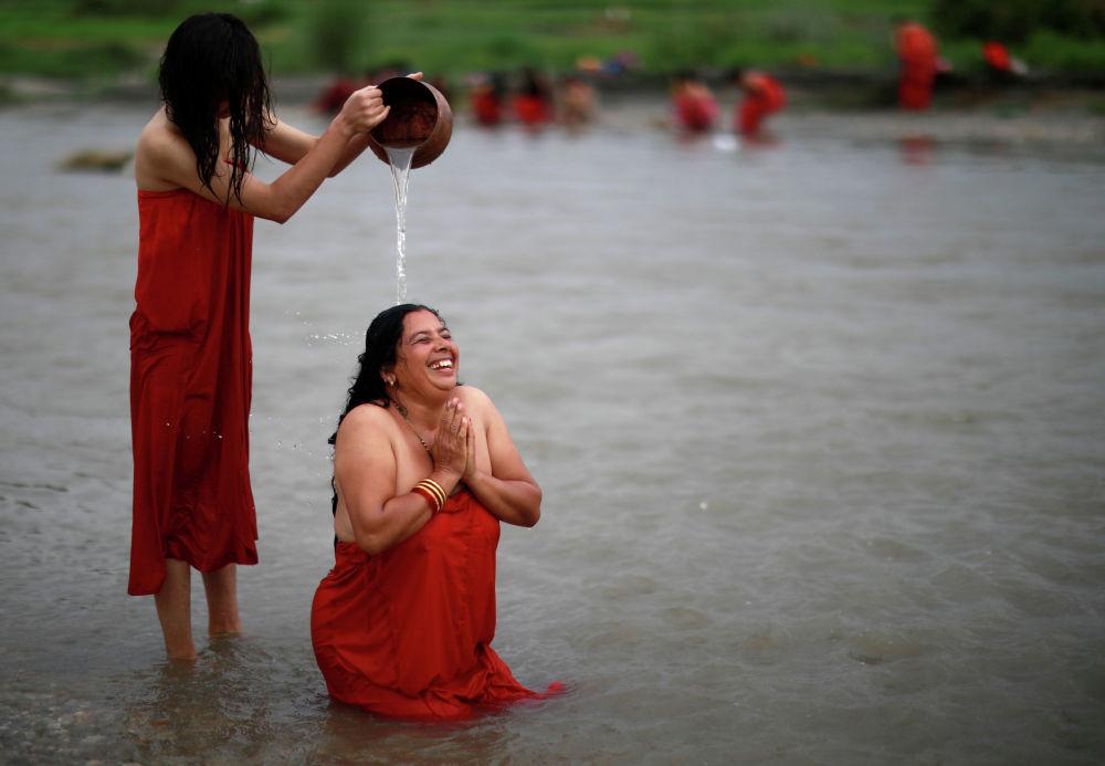 Омовение в реке Манхара во время празднования фестиваля Риши Панчами в Катманду (Непал)