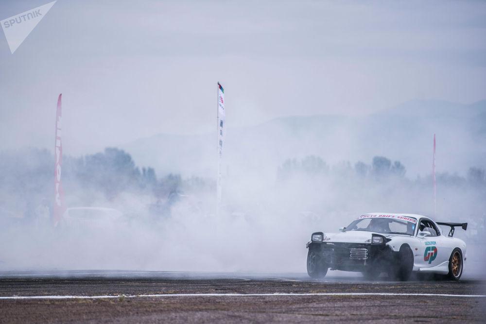 Асманга көк түтүн көтөргөн Mazda RX спорттук унаасы.