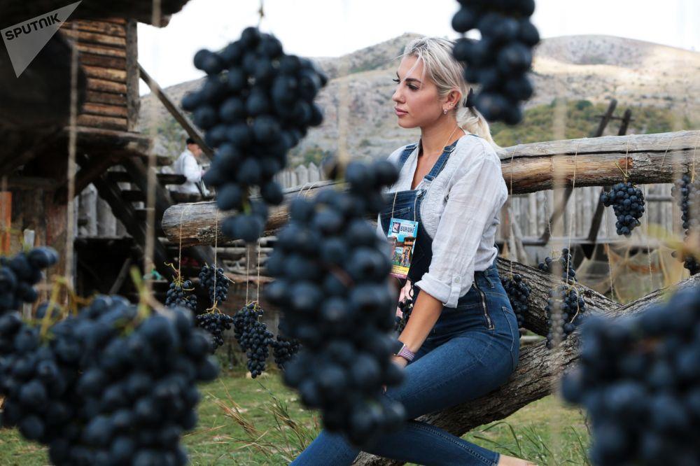Девушка фотографируется в специальной фотозоне на празднике винограда в крымском интерактивном парке Викинг