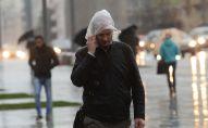 Прохожие идут на Смоленской площади во время дождя в Москве.