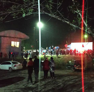 Люди на месте столкновения поезда с пассажирским автобусом в Алматинской области Казахстана.