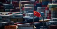 Флаг Китая стоит перед контейнерами в глубоководном порту Яншань, автоматизированном грузовом причале в Шанхае. 9 апреля 2018 года