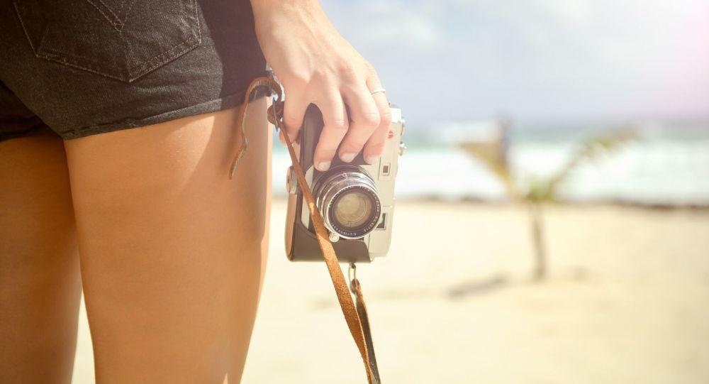 Девушка держит ретро фотоаппарат