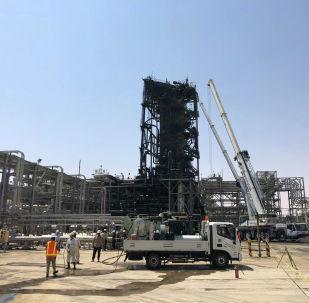 Рабочие видны на поврежденном участке нефтяного завода Saudi Aramco в Хураисе. Саудовская Аравия, 20 сентября 2019 года