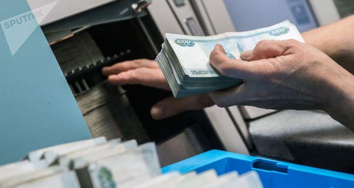 Сотрудница банка считает деньги. Архивное фото
