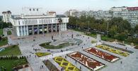 Вид на здание Кыргызской национальной филармонии им. Т. Сатылганова и скульптурный комплекс Манас в Бишкеке
