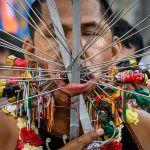 Участник Вегетарианского фестиваля на Пхукете (Таиланд). Фестиваль отличается кровавым ритуалом самоистязания. Мужчины и женщины прокалывают щеки различными предметами. Считается, что боги будут защищать в течение года тех, кто нанес себе увечья во время фестиваля.