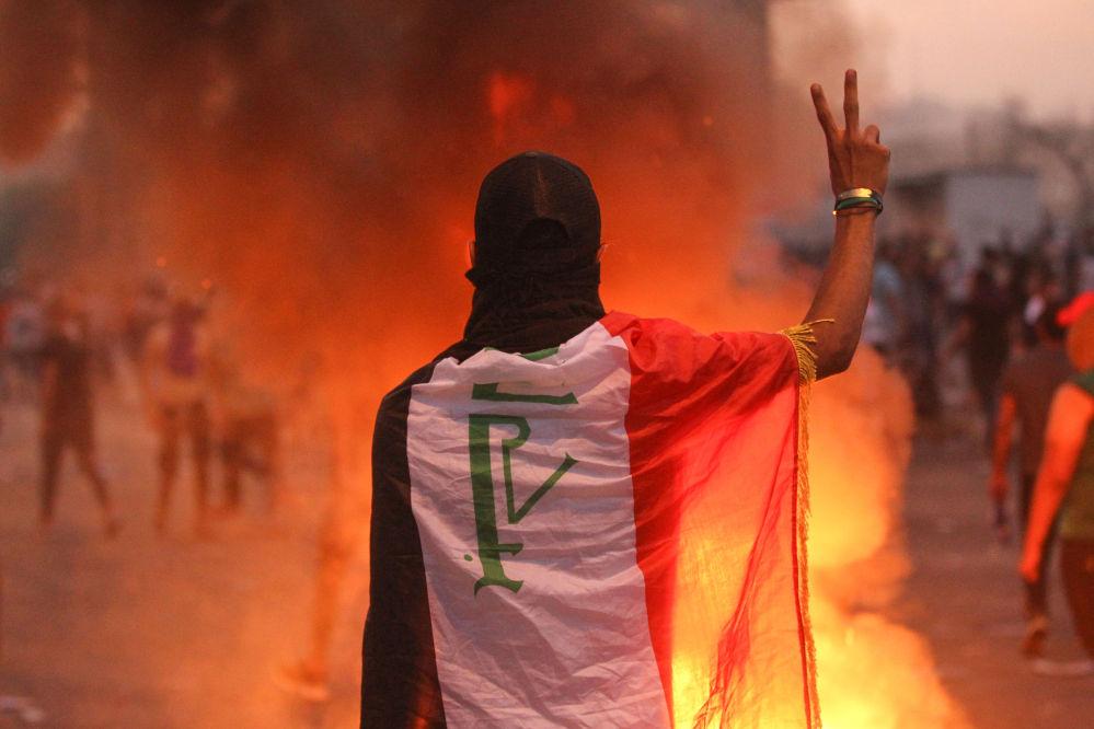 Участник демонстраций против коррупции в государстве, подрыва государственных служб и безработицы на площади в Багдаде (Ирак)