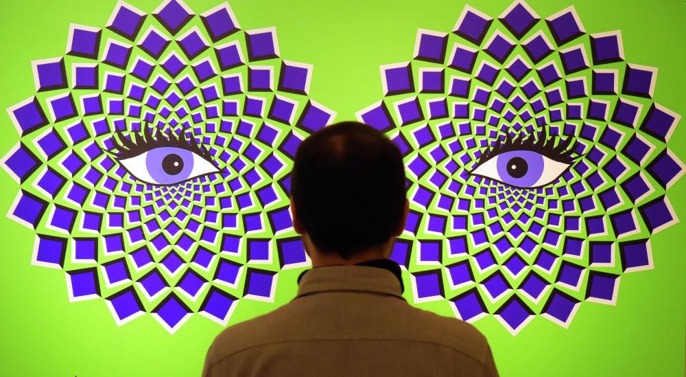 Мужчина стоит напротив экспоната с оптической иллюзией на интерактивной выставке Tricked! в Германии