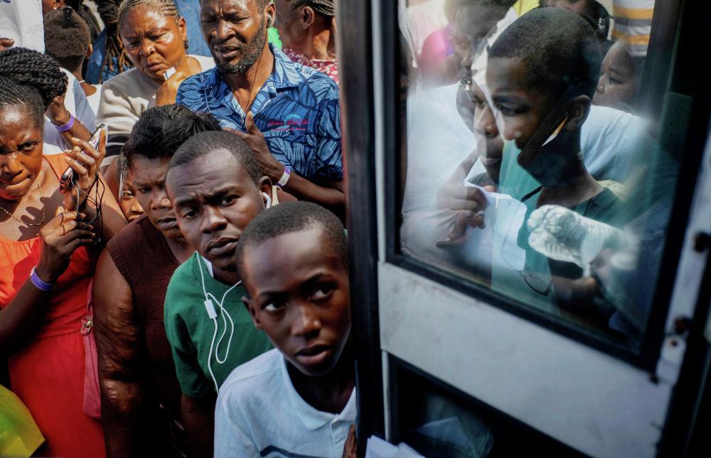 Жители Гаити вернувшиеся домой после урагана Дориан стоят в очереди за гуманитарной помощью. Ураган нанес ущерб на сумму около 7 миллиардов долларов и унес жизни более 50 человек.