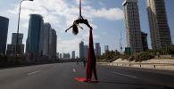 Израильская акробатка выступает посреди шоссе в день праздника Йом Киппур в Тель-Авиве.