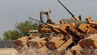 Турецкий военнослужащий стоит на бронетранспортере возле турецко-сирийской границы в провинции Шанлыурфа, Турция, 15 октября 2019 года