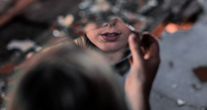 Женщина смотрит в зеркало. Архивное фото