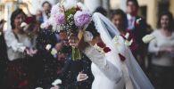 В молодоженых кидают лепестки цветов во время процесса бракосочетания
