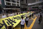 Демонстранты несут плакат с надписью Граждане закрывают свои лица, Кэрри Лэм закрывает свое сердце, когда они идут по улицам во время митинга в Центральном округе Гонконга, пятница, 18 октября 2019 года.