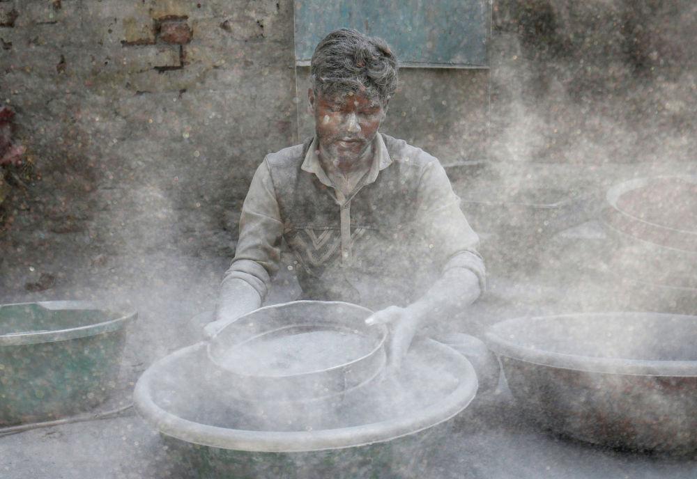 Индиянын от фестивалына даярданып петарда жасап жаткан жумушчу