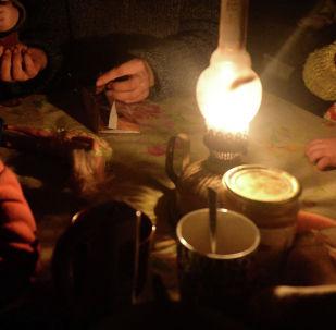 Семья сидят за столом освещенная керосиновой лампой. Архивное фото