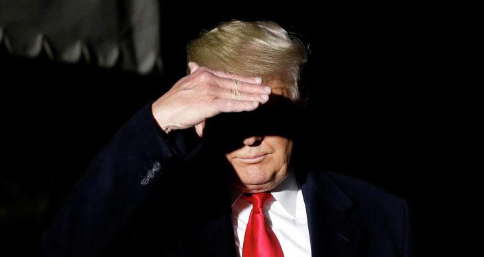 Президент США Дональд Трамп закрывает лицо от телевизионных огней, когда он идет по южной лужайке Белого дома в Вашингтоне. США, 2 ноября 2019 года