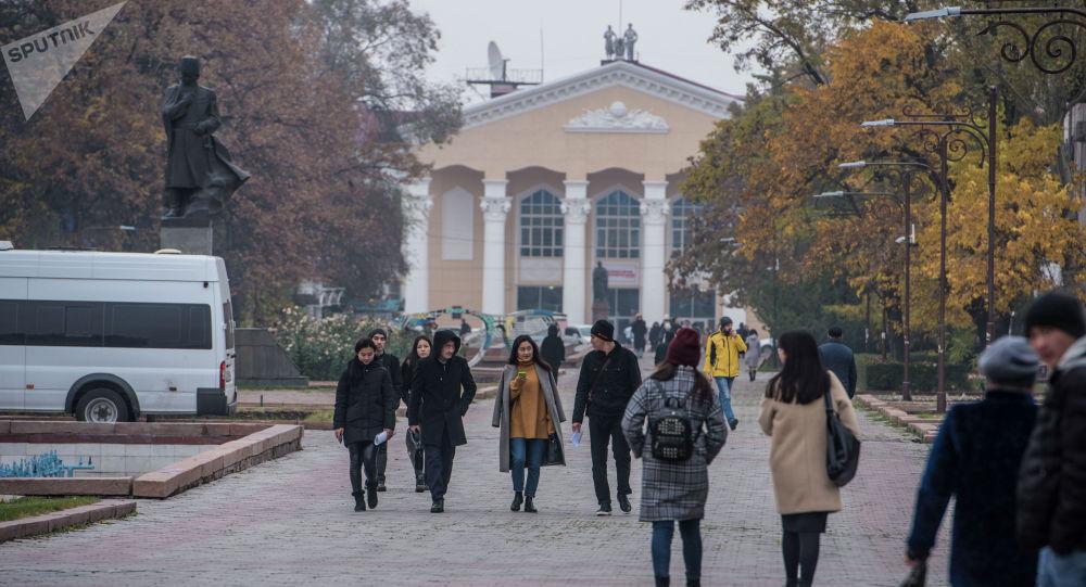 Люди идут по аллее молодежи во время осенних холодов в Бишкеке