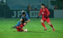 Футболисты во время матча отборочного раунда чемпионата мира 2022 года между сборными Кыргызстана и Японии на стадионе Омурзакова в Бишкеке.